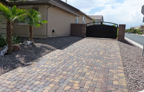 iron metal gate and stone paver driveway